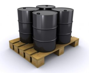 Four black oil barrels on a wooden pallet